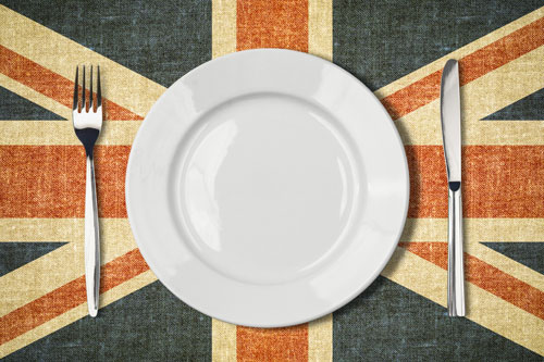 A knife, fork and plate are laid on a British Flag