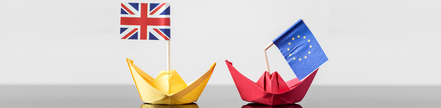 Paper boats with a UK flag and broken EU flag