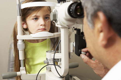 Optician In Surgery Giving Girl Eye Test