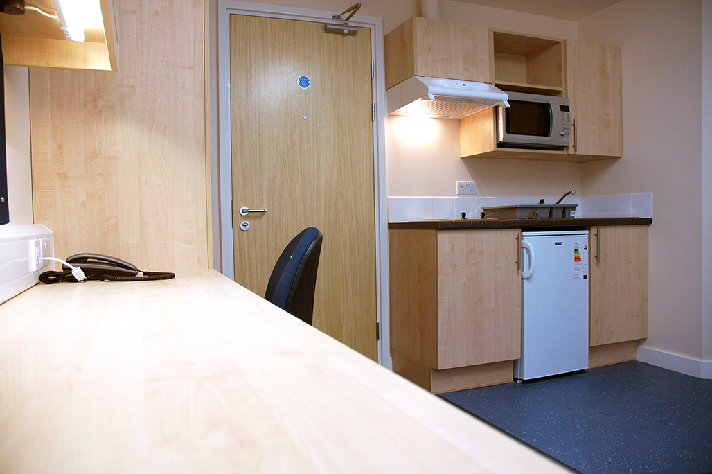 View of a studio room showing the desk, entrance door and kitchen area. The door is a fire door with a closer. The kitchen area has dark blue laminate flooring.