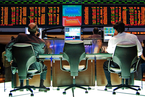 Two men work at their desks in front of stock exchange boards