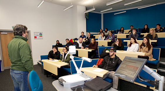 A male lecturer with a lecture theatre of students