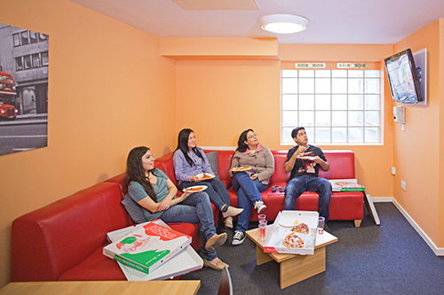 Common Room. Four students on a red corner sofa watching a wall mounted TV.