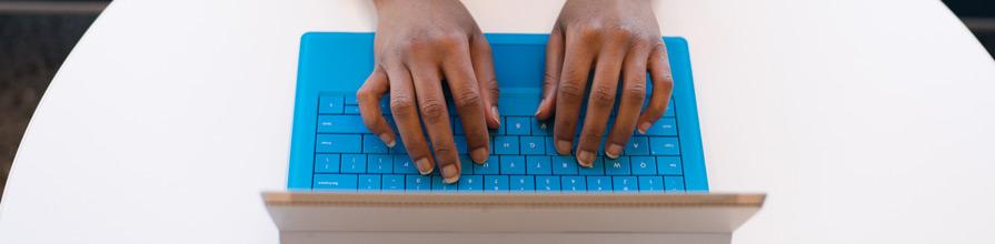 Woman typing on Microsoft surface