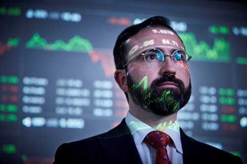 Man with stock market figures reflecting on his face