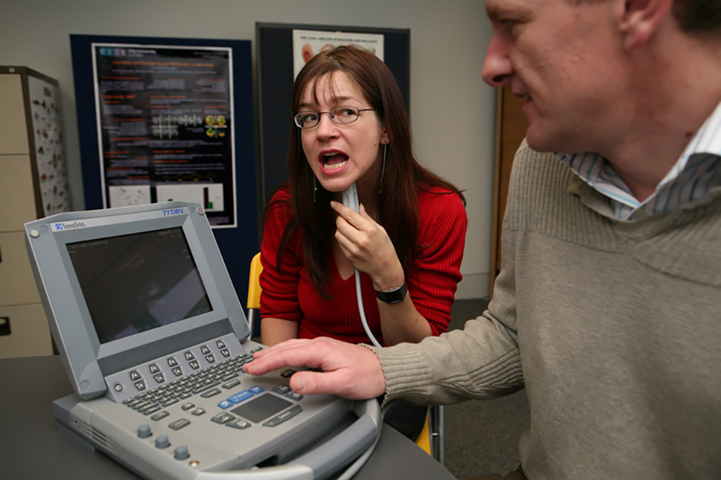Woman holds portable ultrasound application by her throat as man looks at screen