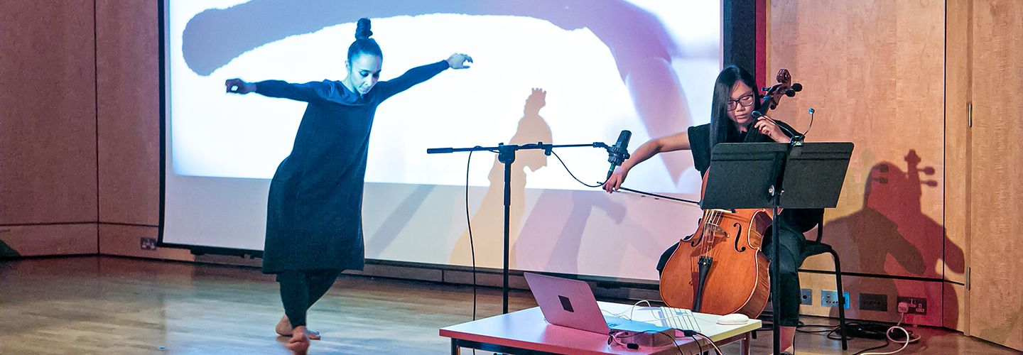 City Summer Sounds Festival MA Showcase - dancer and cellist on stage with video backdrop showing a Chinese calligraphy brush writing a horizontal line.