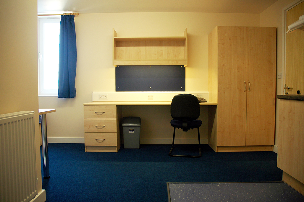View of a studio room showing the wide desk and wardrobe. There is also a radiator visible facing the kitchen area.