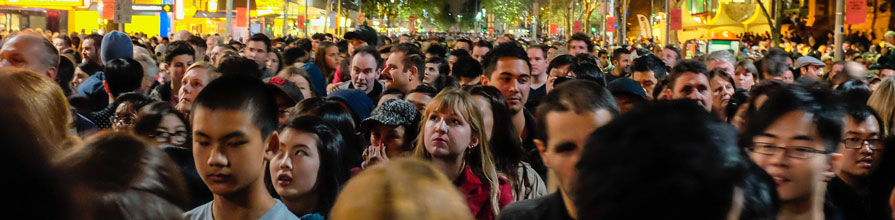 A blonde woman looks up while standing in the center of a busy crowd at night