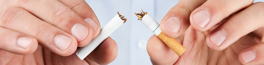 Two hands break a cigarette in half