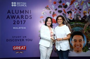 Mary Ann Ooi Suan Kim, City Law School, in front of a poster at the British Council Alumni Awards 2017 in Malaysia.