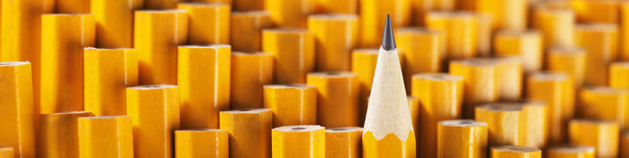 A single sharpened pencil stands tall above a group of blunt pencils