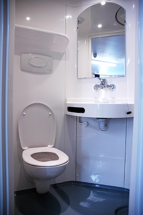 Interior of the en-suite bathroom showing the built-in toilet and sink with a mirror above it, all in clean white.
