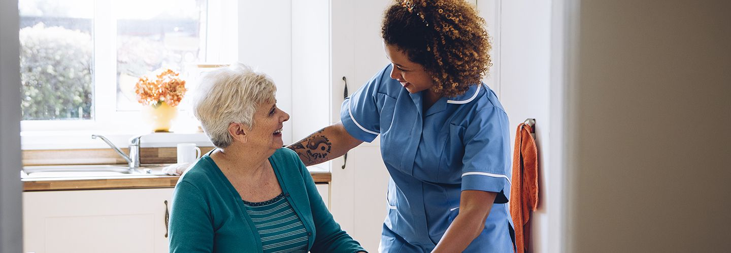 An elderly white lady sitting smiles up at a young black nurse standing beside her, who smiles back.