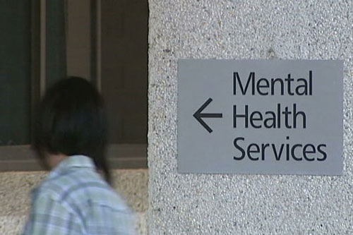 A person walks past a sign pointing to mental health services