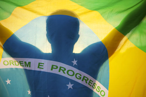 Silhouette of a man holding up and standing behind the Brazilian flag