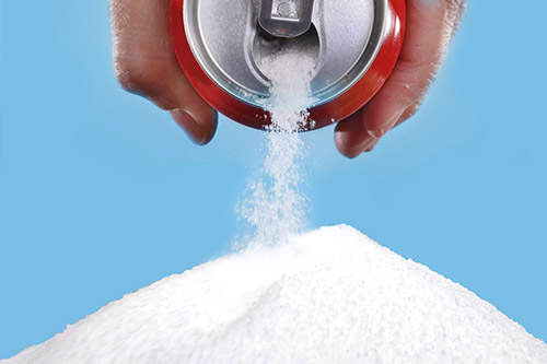 Looking at Sugar Tax in the UK a coca cola can pours out white sugar.