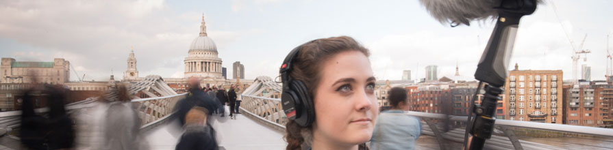 A City University London Music BSc student holds a boom mic on a London bridge