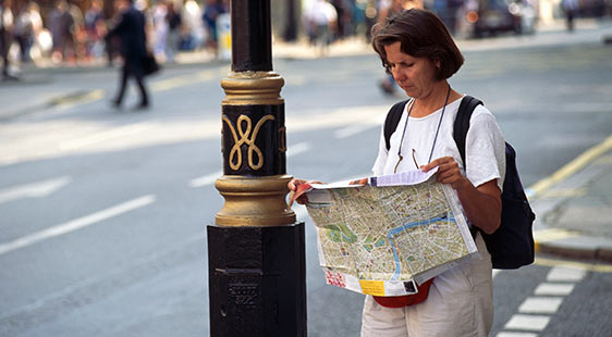 A woman reading a map on a London street