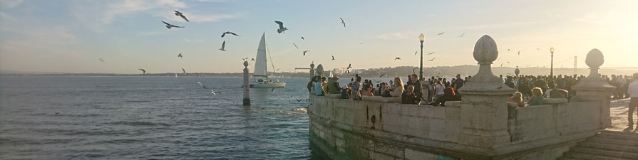 Crowds of people gather around Lisbon's famous seafront.